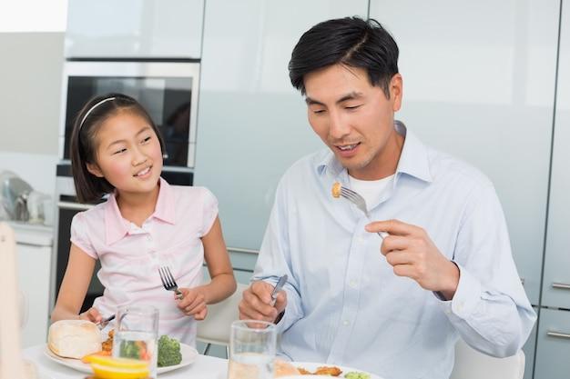 父を見ている少女は台所のフォークで食べ物を食べる