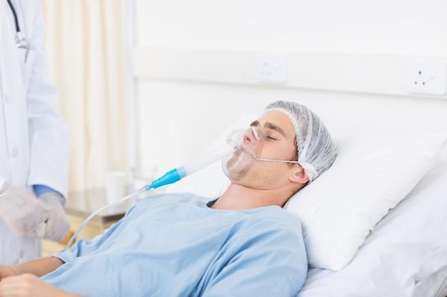 Мужской врач, корректирующий кислородную маску пациента