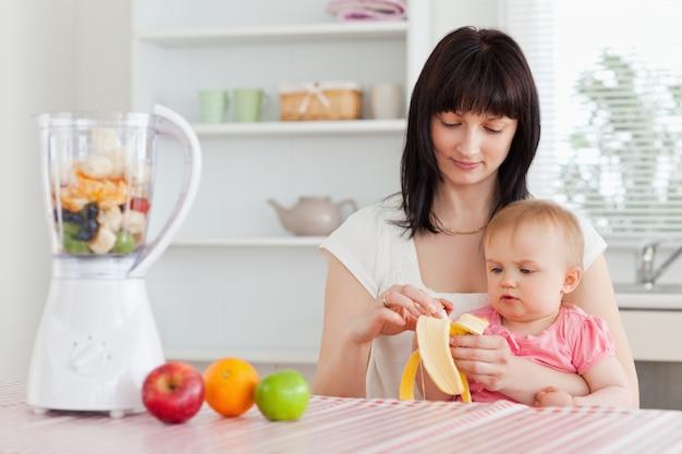彼女の赤ちゃんを彼女の膝の上にキッチンで持っている間、バナナをピーリングする豪華なブルネットの女性
