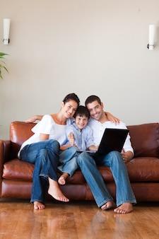 両親と子供は、親指とコピースペースでラップトップを使用して