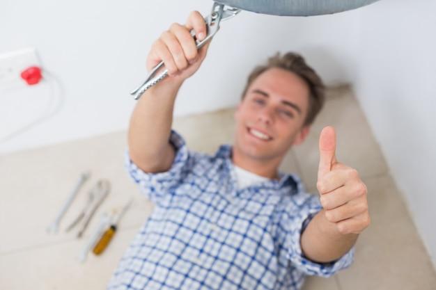 湯沸かし器の下で技術者の身振りの親指