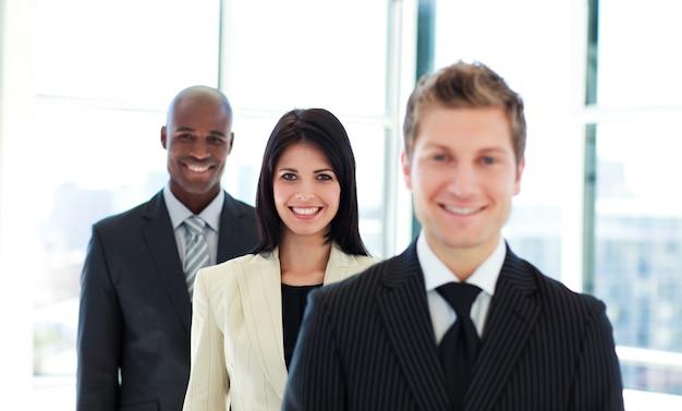 Улыбаясь бизнесмен в фокусе с ее командой