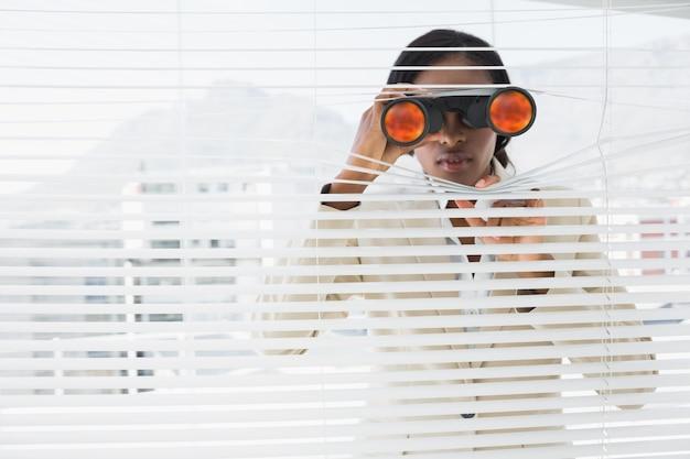 ビジネスマン、双眼鏡、ブラインドで覗いている