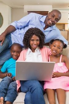 ラップトップを使ってソファーでリラックスした幸せな家族