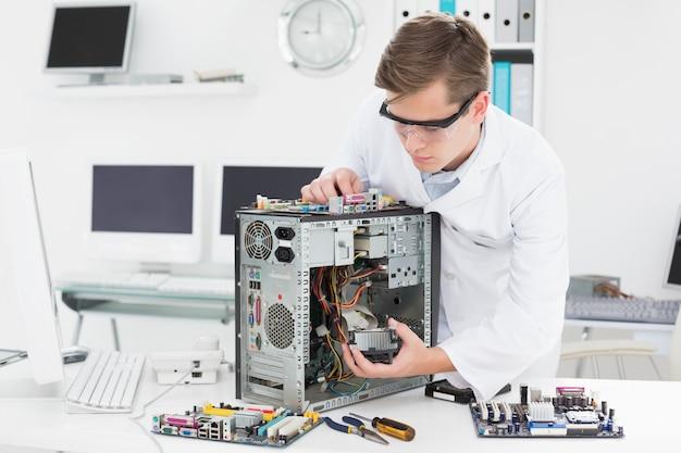 壊れたコンピュータで働く若い技術者