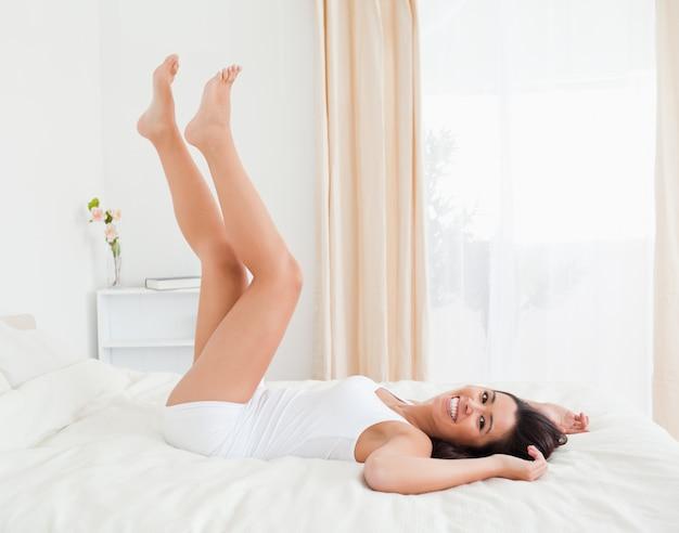 Улыбающиеся женщины ноги подняты высоко и руки под головой, лежа на кровати