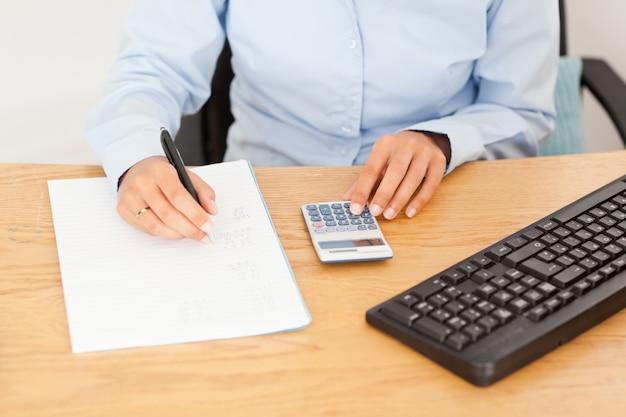 女性の会計士は、紙の上に結果を書いて