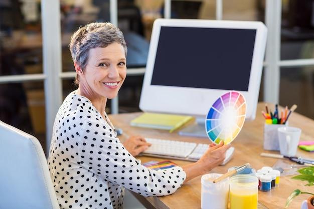 コンピュータとカラーチャートで作業するカジュアルな実業家