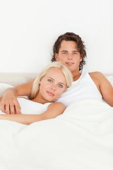 ベッドに横たわっているかわいいカップル