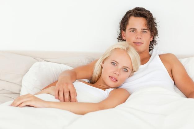 ベッドに横たわっている穏やかなカップル