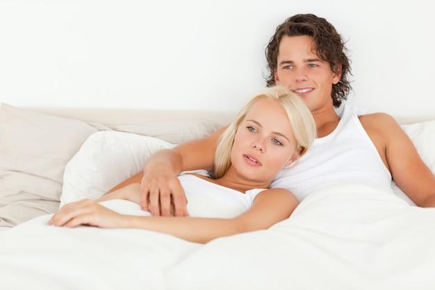 ベッドに横たわっている幸せなカップル