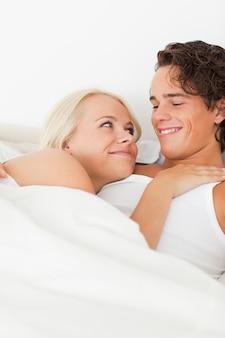 抱き合っているベッドに横たわっている夫婦の肖像