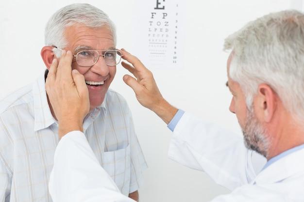 Человек в очках после проведения осмотра зрения у врача