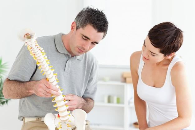 カイロプラクティックと患者の背骨のモデルを見て