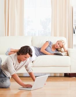 Портрет человека, используя ноутбук, пока его девушка читает