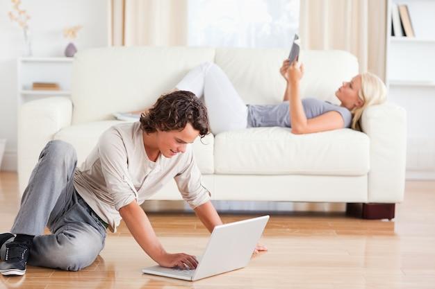 Человек, используя ноутбук, пока его девушка читает книгу