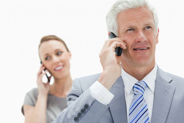 白い髪のビジネスマンの笑顔の女性と電話で話す