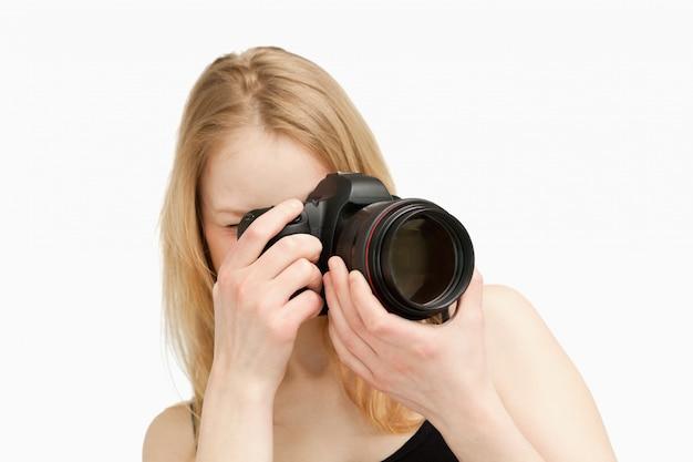 一眼レフカメラで撮影している女性