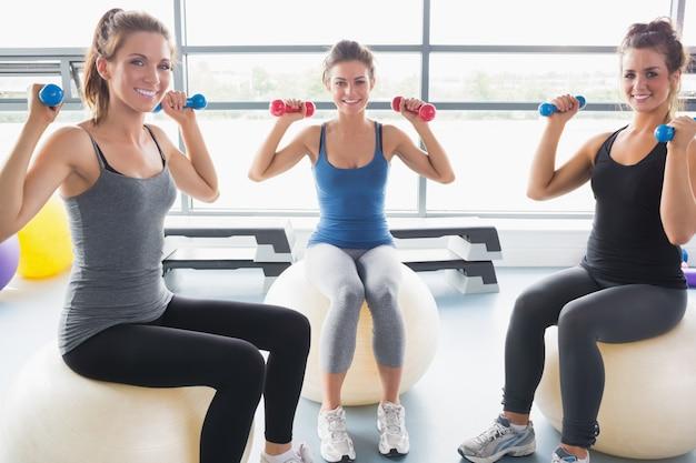 運動のボールに重量を持ち上げて笑顔の女性
