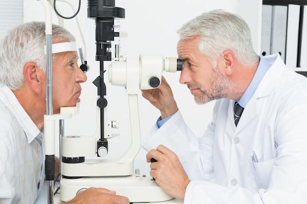 シニア患者の視力検査を行う検眼官