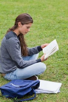 十字架に座っている間に本を読んでいる若い深刻な女の子