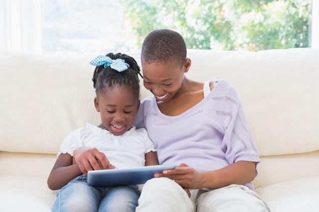 Счастливый улыбается мать, используя планшет с дочерью на диване