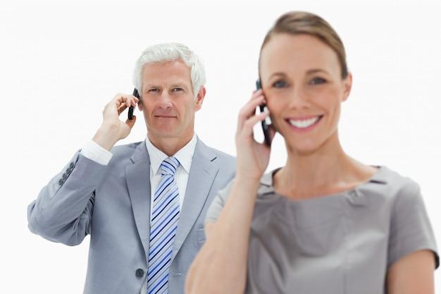 笑顔の女性と電話をかける白髪のビジネスマンのクローズアップ