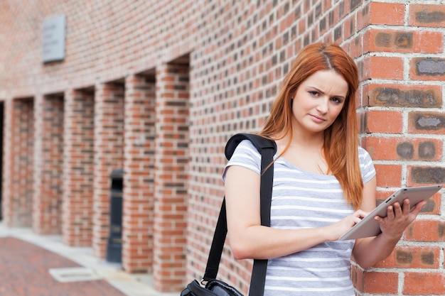 Серьезный студент, держащий планшетный компьютер