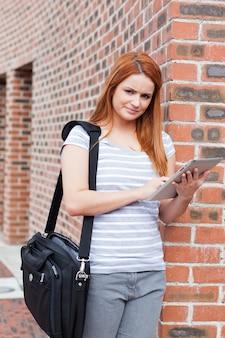 Портрет серьезного студента, держащего планшетный компьютер