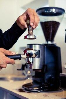 Бариста прижимает свежую кофейную гущу