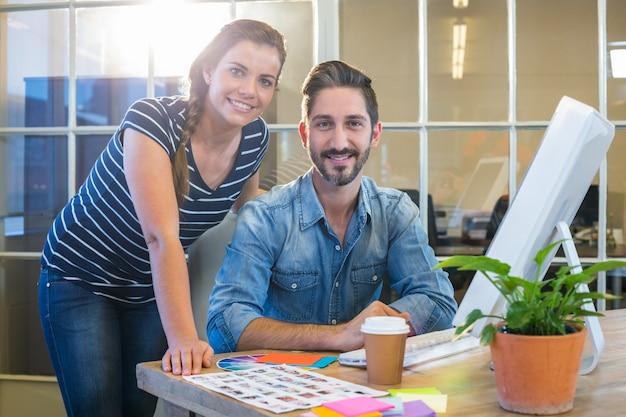 コンピュータで一緒に働く笑顔の同僚