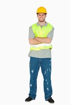 Улыбаясь молодой строитель со сложенными руками