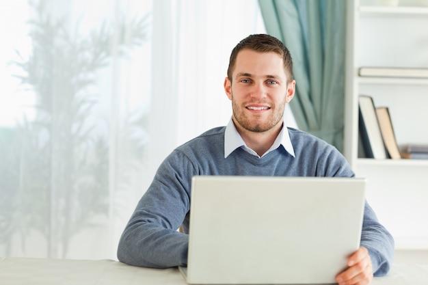 彼のホームオフィスでノートを持っている男