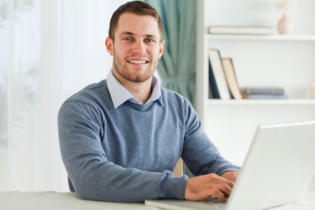 彼のホームオフィスでラップトップと笑顔のビジネスマン