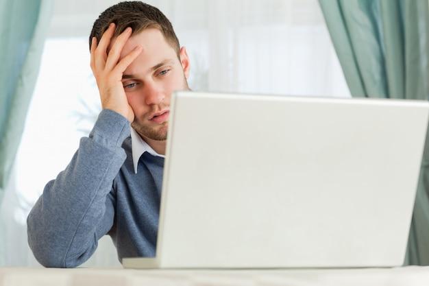 彼のホームオフィスでノートパソコンで迷惑をかけるビジネスマン