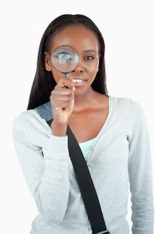 拡大鏡で笑顔の若い女性