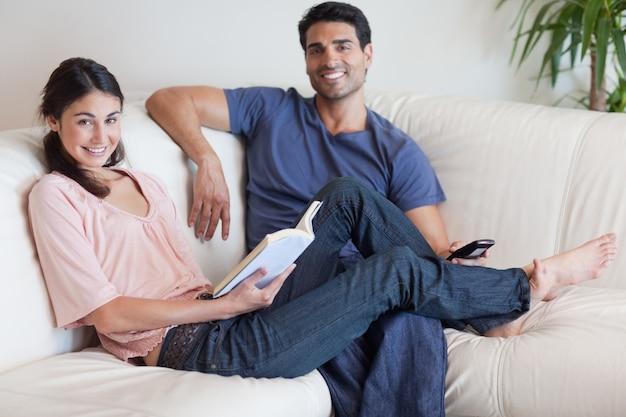 Женщина читает книгу, пока ее муж смотрит телевизор