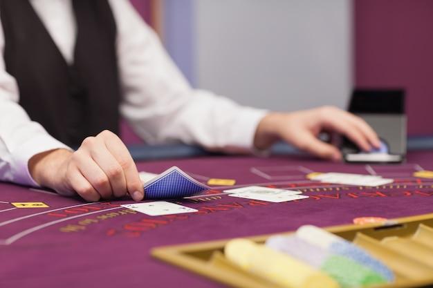 テーブルにカードを配布するディーラー