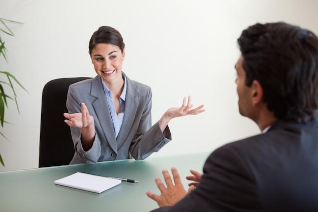 従業員にインタビューする笑顔のマネージャー