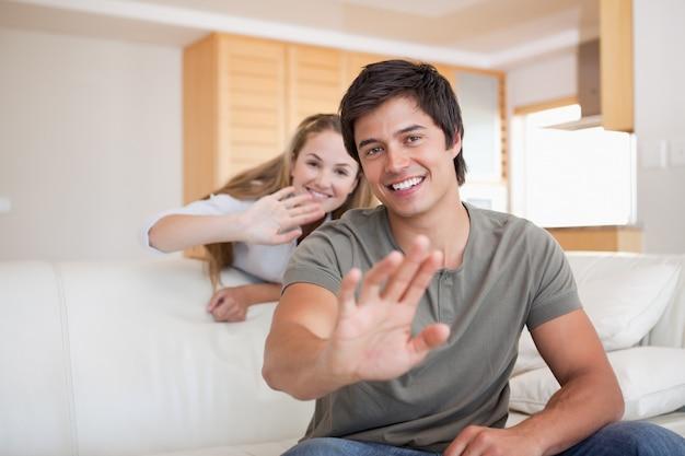 カメラで手を振るカップル