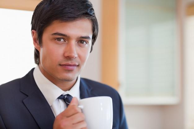 コーヒーを飲む、ハンサムなビジネスマンのクローズアップ