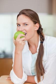 リンゴを食べる健康な女性の肖像