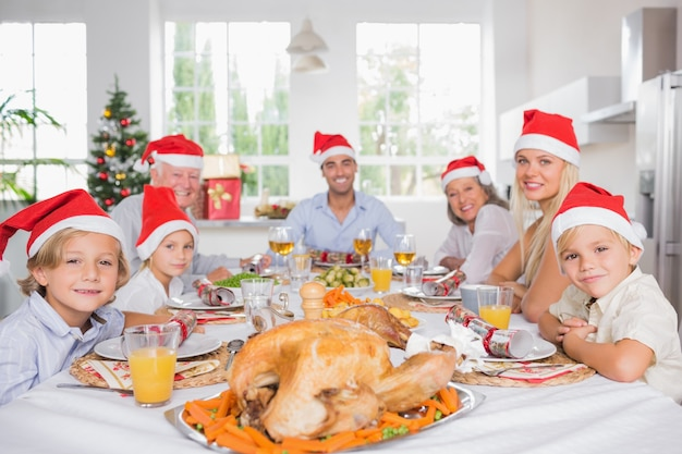 夕食のテーブルの周りにサンタの帽子を着ている幸せな家族