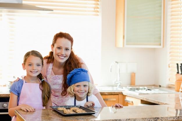 キッチンに子供とクッキーを持つ母親