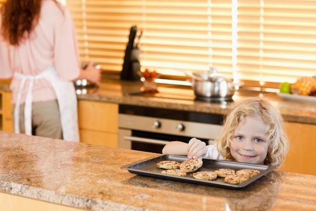 母親が見ていない間にクッキーを盗んでいる少年