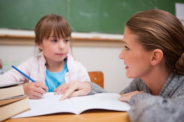 彼女の先生が話している間に書いている女子学生