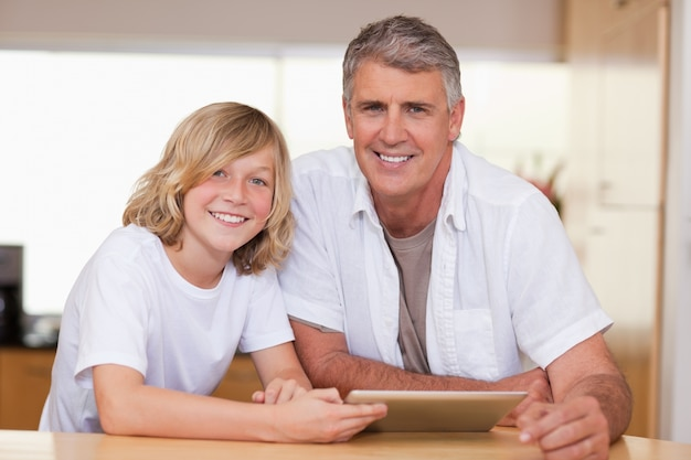 少年と父親はタブレットを使っている