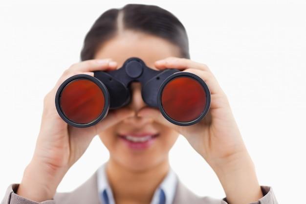 双眼鏡を介して見ているビジネスマンのクローズアップ