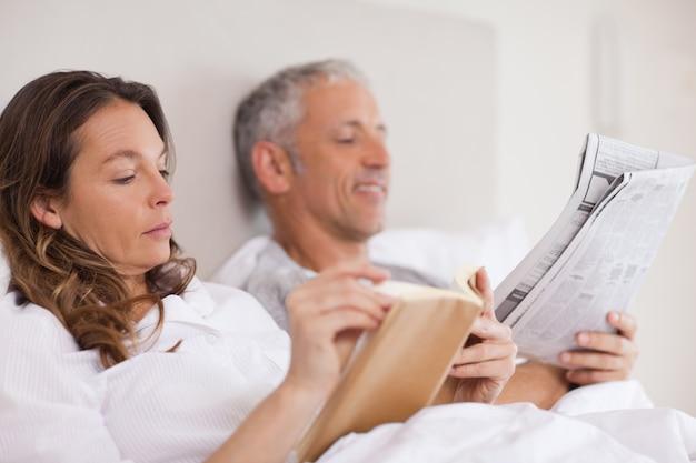 Женщина читает книгу, пока ее муж читает газету