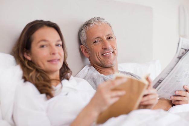 Счастливая женщина читает книгу, пока ее муж читает новости